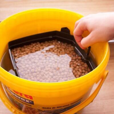 Afbeelding: Aquarium potfilter filtermateriaal schoonspoelen in emmer